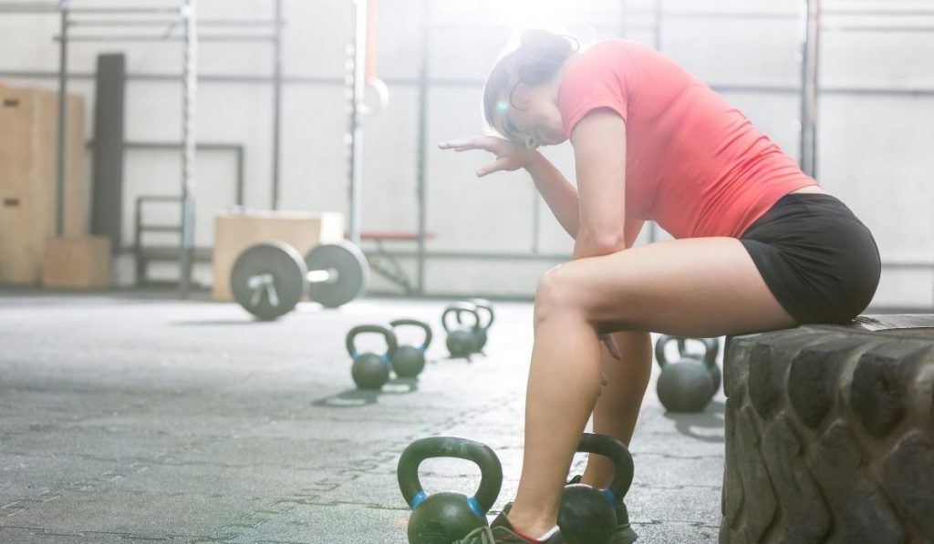 Exhausted women in CrossFit gym