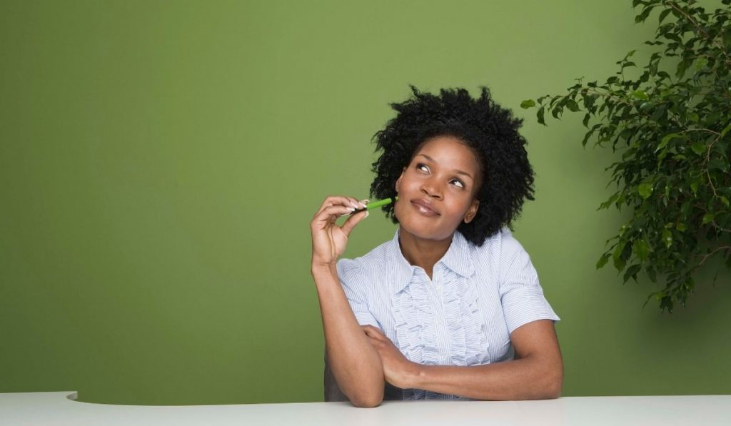 african american woman daydreaming with a green wall and plants in the background