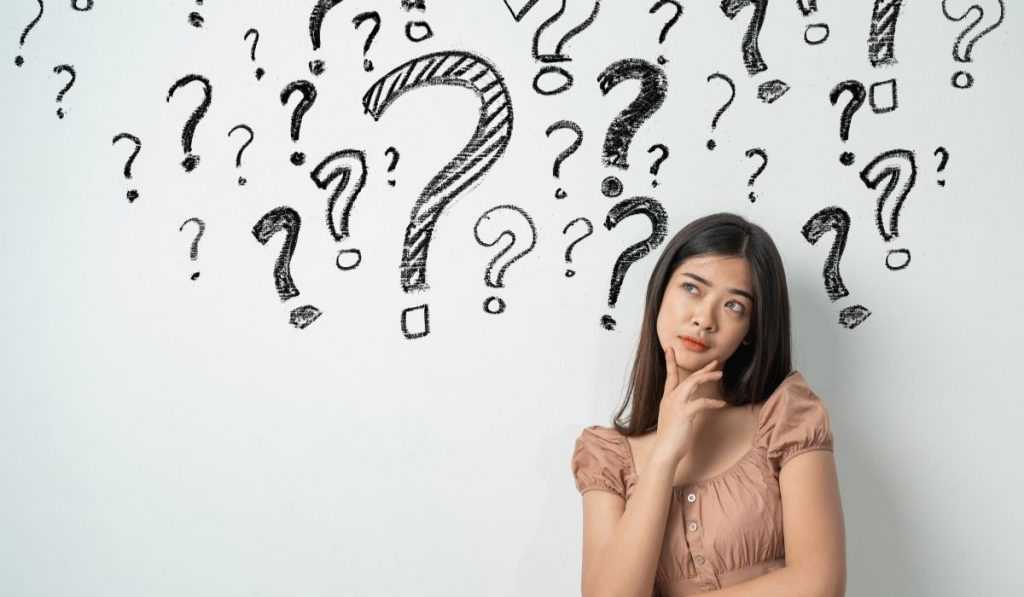 asian girl in beige blouse with question marks in the background