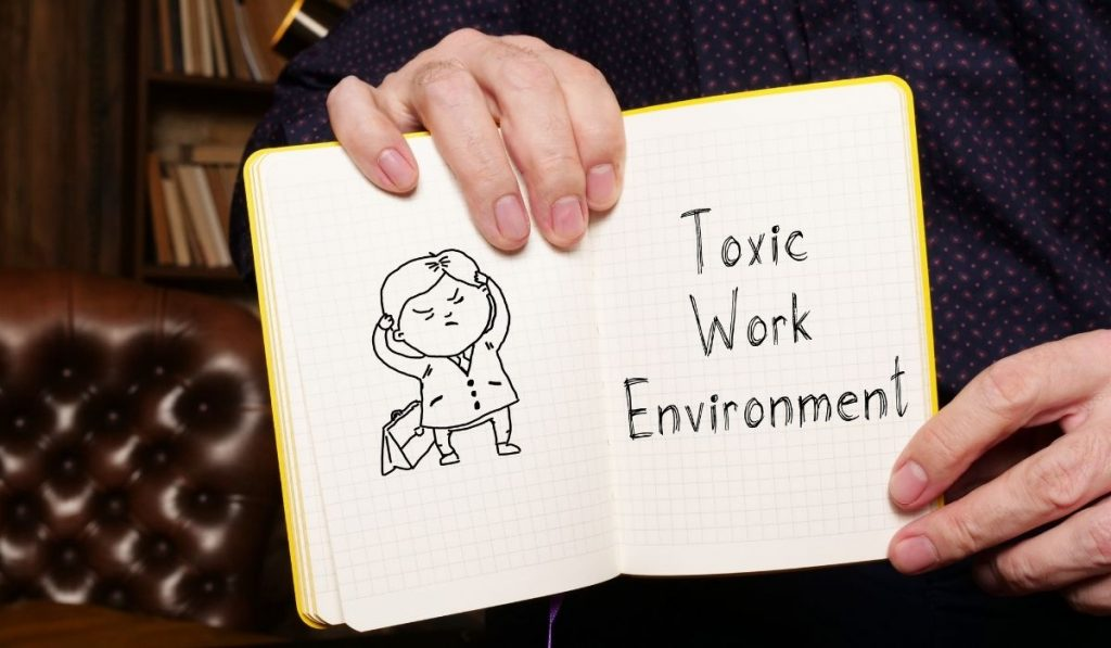 caricature of a man and the words toxic work environment written on a yellow notebook