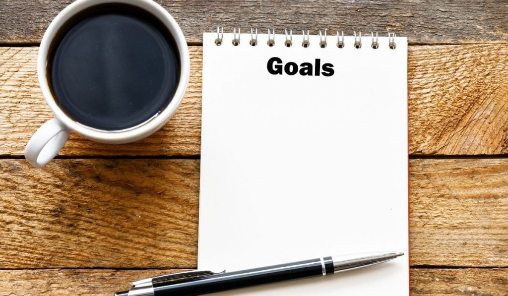 a notepad for goal setting, pen and a cup of coffee