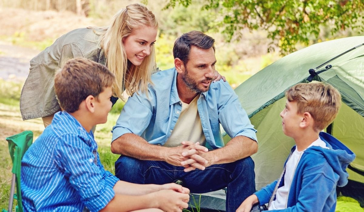 parents share stories to their kids while camping in the woods