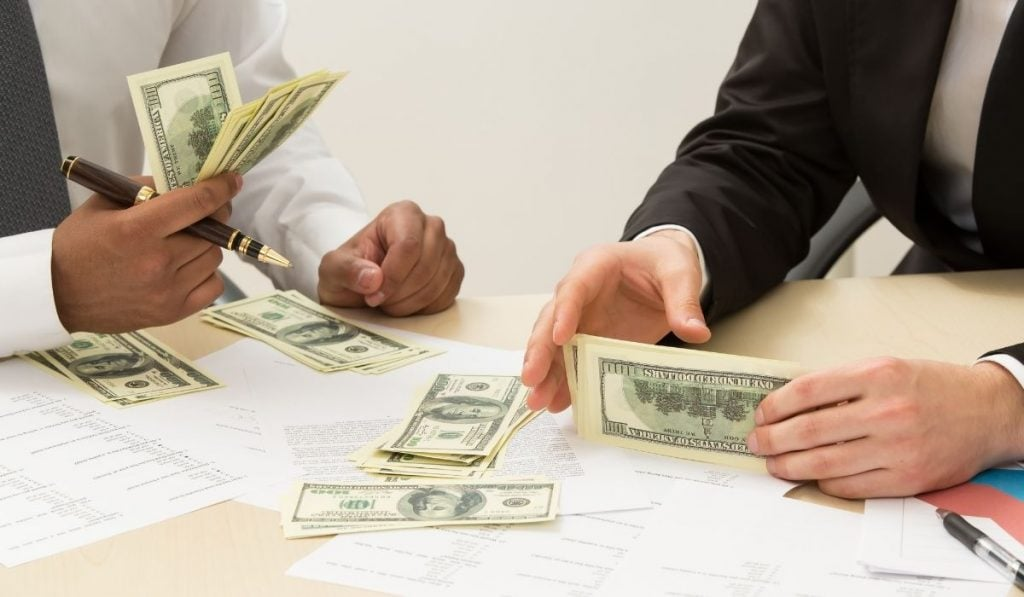professionals holding money and budgeting to pay for bills