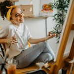 teenager girl happily painting a portrait as her hobby