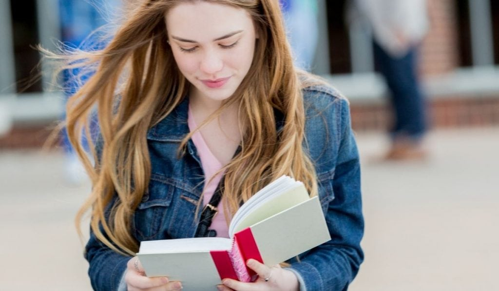 teenager reading a book to stay productive