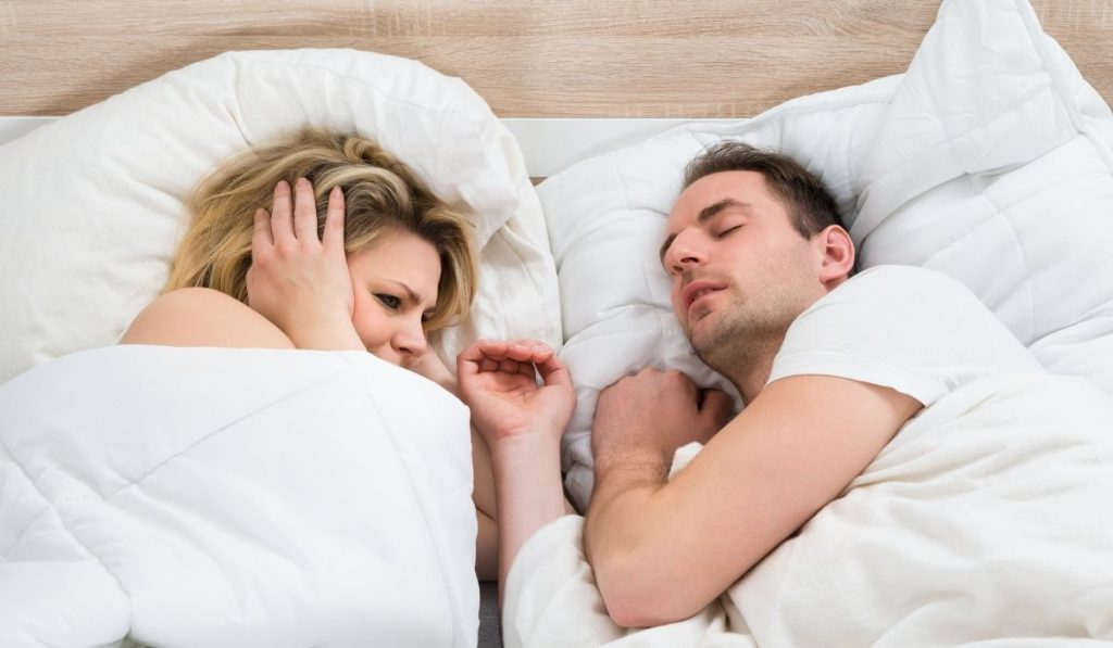 woman covering her ears while a man is snoring beside her