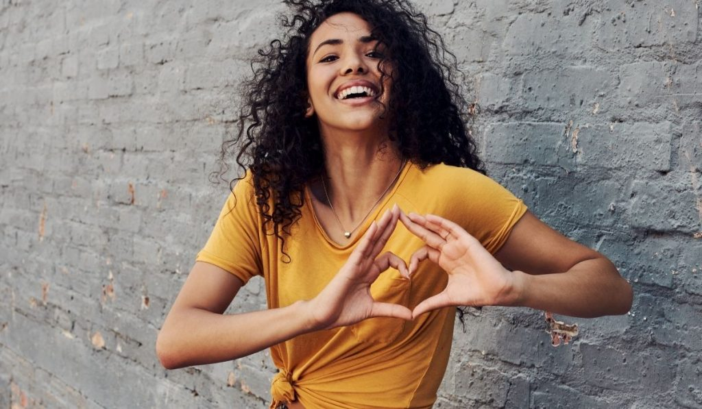 a happy young woman making a heart sign gesture