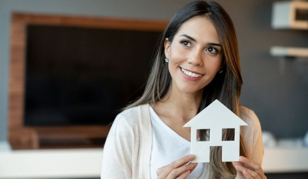 a woman holding a cut out cardboard house. manifesting in buying a house.