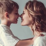mom and son face to face touching their noses and smiling