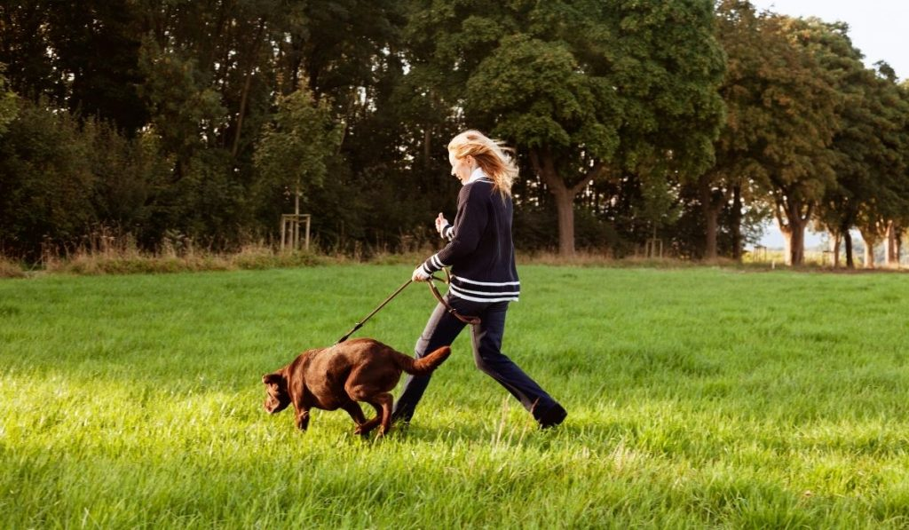 young-woman-running-with-dog
