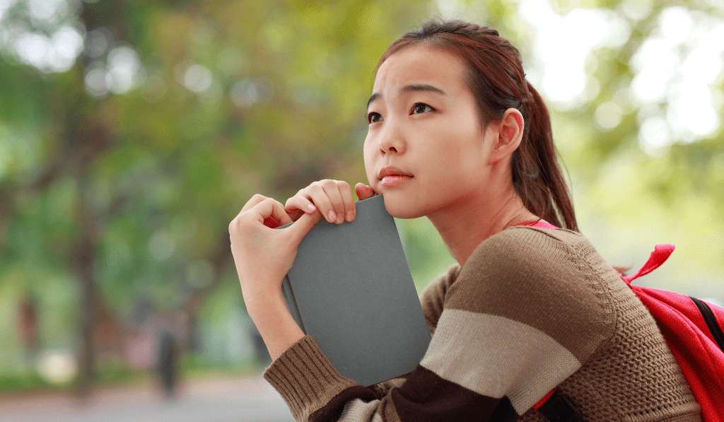 Girl sitting holding a notebook.
