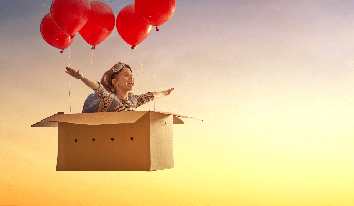 little girl dreaming of flying in a box with balloons attached to it
