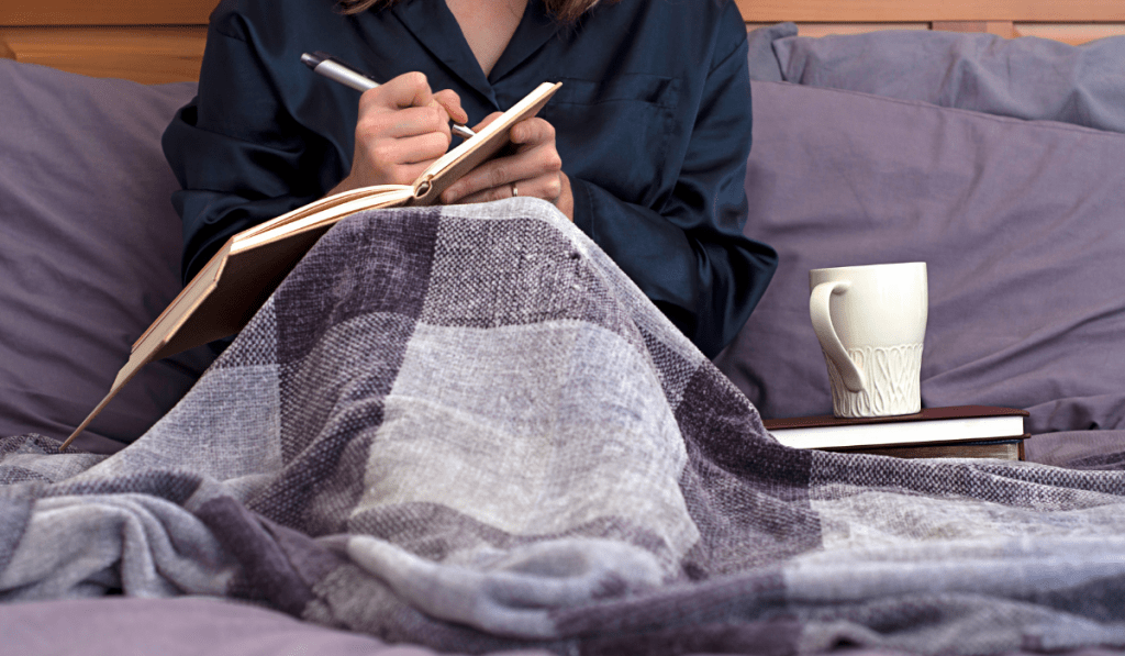girl writing a journal with a cup of coffee in her bed