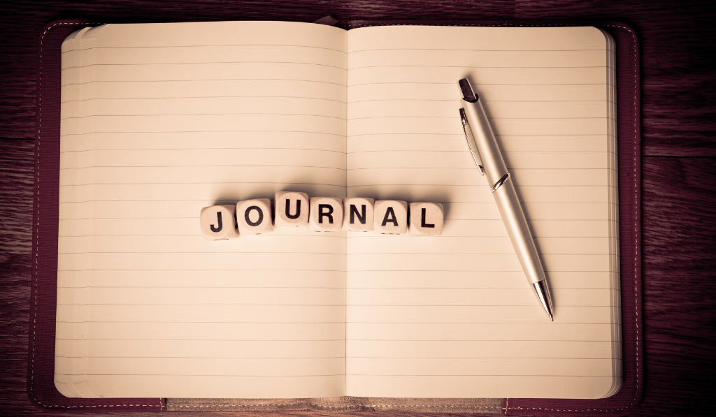 A journal word in letter blocks beside a pen on top of a journal notebook