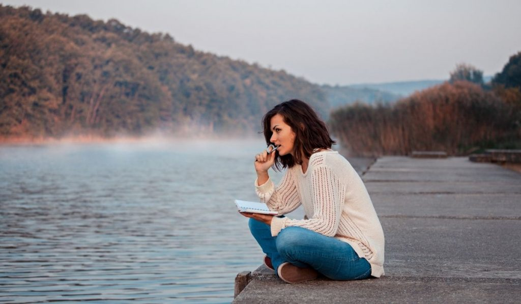 woman by the lake with a pen in her mouth, holding a notebook and thinking of something to write about