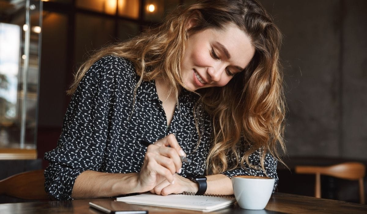 woman in a restaurant writing with her cup of coffee