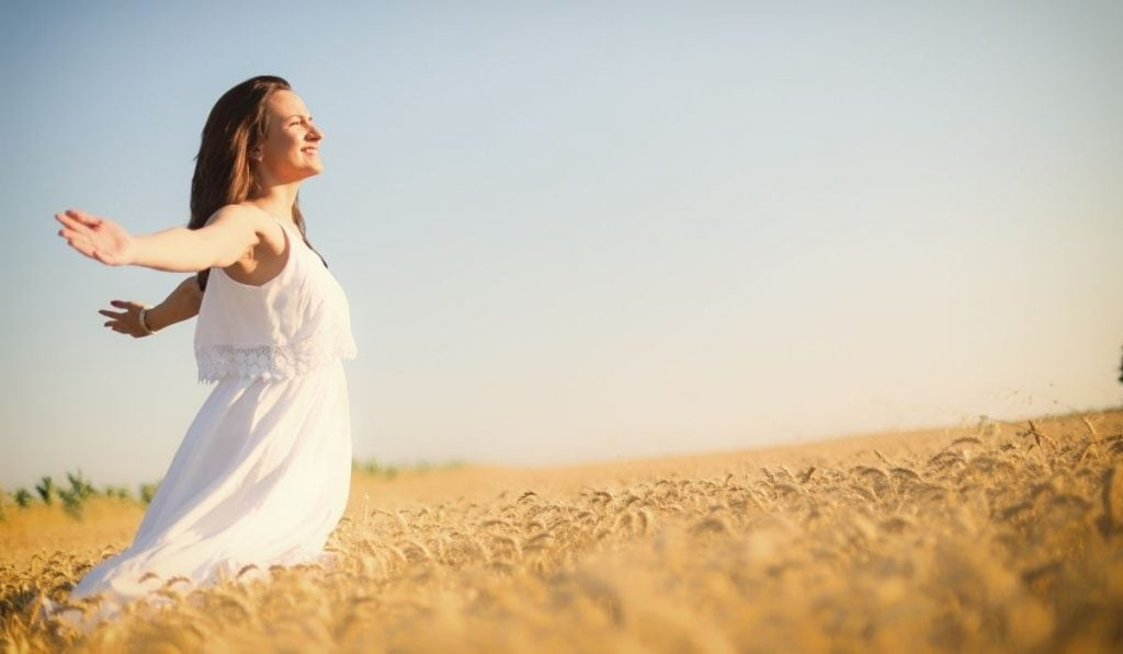 woman standing in a wheat field with arms wide open