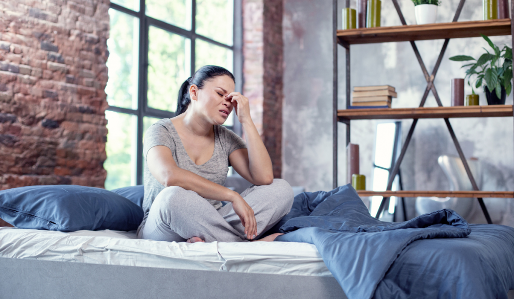 A woman sitting in the bed feeling exhausted